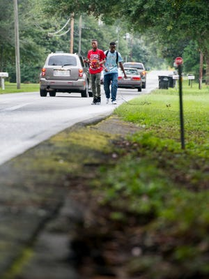 Cars drive around Trae Calhoun, 14, left, and  Malik Griggs, 17, as they walk home from Booker T. Washington High School on East Burgess Road in Pensacola on Thursday, August 10, 2017.  Because there are no sidewalks on East Burgess Road between North Davis Highway and Sanders St., students often walk in the road especially on rainy days like today when the roadsides are muddy.