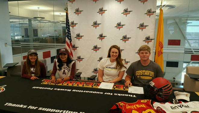 Four Centennial High School athletes signed to play college sports on Monday in the CHS library. Corinne Hanson, left, and Leah Salazar, second from left, signed to run track at New Mexico State while Savannah Bush, second from right, signed to play volleyball at Division III Emery University in Atlanta and Jake Boykin, right, signed to play football at Division III Gustavus Adolphus College in St. Paul, Minn.