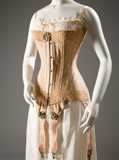 "This image released by The Museum at FIT shows Corset, floral brocaded silk, silk ribbon, elastic, circa 1905, England. From a 1770 corset to a 2014 bra-and-panty set in lacy stretch silk, the Museum at the Fashion Institute of Technology has taken on lingerie and ladies foundation garments as the focus of a new exhibition. In about 70 pieces, ""Exposed: A History of Lingerie"" touches on the mechanics, marketing and cultural touchstones that not only shape and adorn but helped define culture around the globe. For more stories and photos, see the July