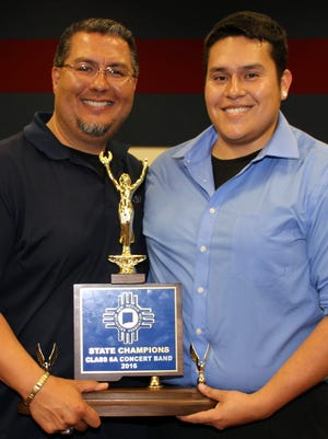 Deming High School Athletic/Activities Director Bernie Chavez, left, and DHS Band Director Sergio Beraun hold the 2016 New Mexico Class 6A State Concert Band Championship Trophy, the school's ninth in 11 years. This past band season the student musician also made it five state titles in a row. Chavez, the former band leader for eight of those state titles, handed over the baton to Beraun who has maintained a high-standard of success in the DHS band room. Beraun and the Wildcat Marching Band will give a sneak peek of this year's sound during the Concert on the Green at 6 p.m. on Friday in front of the DHS Main Campus. The public is invited and advised to bring lawn chairs and/or blankets to sit on the lawn at Wildcat Circle Drive.
