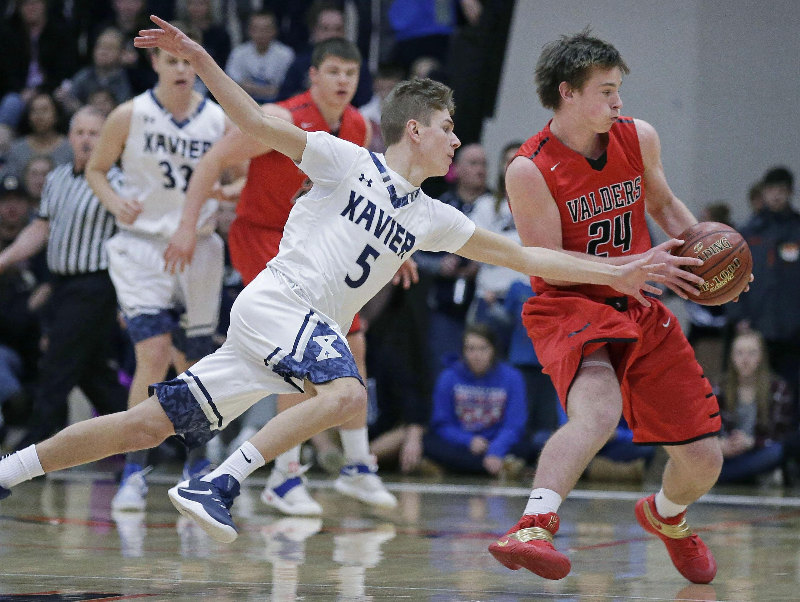 Sam Ferris, left, of Xavier reaches for the ball held by Fletcher Dallas of Valders during a WIAA Division 3 sectional championship game Saturday night in Kaukauna.