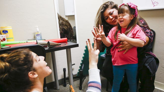 Byanca Carrasco is helped by her mother, Ramona, during an exercise in a musical-therapy session led by Lorena Hernandez on Feb. 3, 2016, at Musical Surprise in Surprise. Byanca, who was born with Down syndrome, is able to attend the musical-therapy program with her mother through the Empowerment Scholarship Account program.