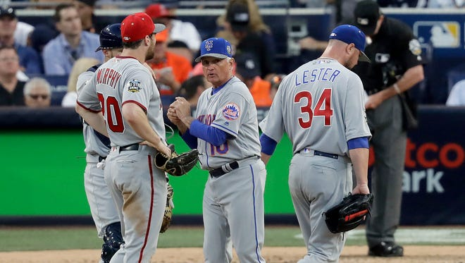 National League manager Terry Collins of the  pulls  Jon Lester of the Chicago Cubs during the seventh inning of the MLB baseball All-Star Game as Daniel Murphy of the Washington Nationals looks on.