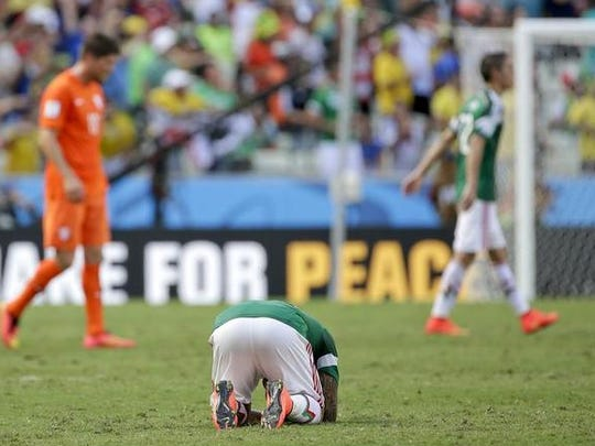 Mexico's Javier Aquino lies on the pitch after the Netherlands defeated Mexico 2-1 to advance to the quarterfinals during the World Cup round of 16 soccer match between the Netherlands and Mexico at the Arena Castelao in Fortaleza, Brazil, Sunday, June 29, 2014.