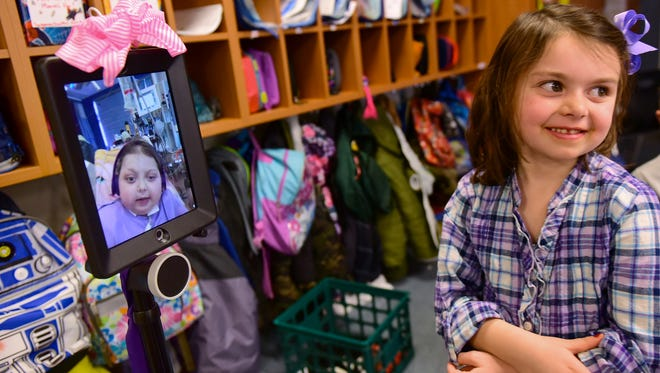 Reese Burdette, left, chats with her sister, Brinkley, using her robot in class at Mercersburg Elementary School Thursday, Jan. 21, 2016. Reese is being treated for an illness at  John Hopkins Medical Center Baltimore, Md., but she can maneuver through the school using the robot.