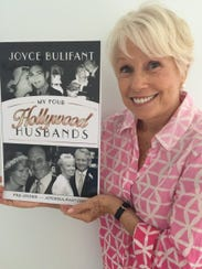 Joyce Bulifant displaying the cover of her book, My
