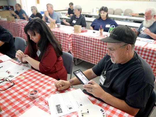 Robert Husted from the Kitsap County Search & Rescue and the South Kitsap CERT, takes a camera phone photo of his painted make-up injury at the Moulage Mayhem class on Saturday at the Central Kitsap Fire and Rescue Station 41.