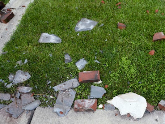 Bricks and concrete lay on the grass and sidewalk after the lightning strike. Nancy Callen small parts of the building which flew off the tower damaged her car, but she was most thankful that nobody was hurt.