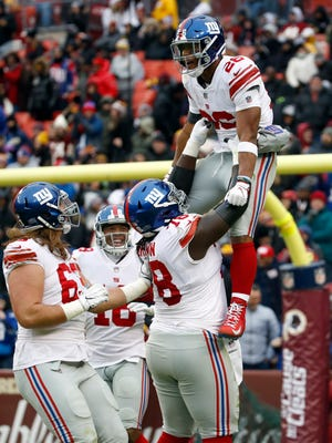 New York Giants running back Saquon Barkley (26) is picked up offensive guard Jamon Brown (78) as they celebrate his 78-yard touchdown during the first half of an NFL football game against the Washington Redskins, Sunday, Dec. 9, 2018, in Landover, Md. (AP Photo/Patrick Semansky)
