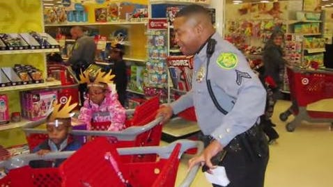 Dover Police Cpl. Carlton Turner takes at-risk youngsters shopping in last year's Heroes & Helpers project, now seeking donations to finance children's holiday shopping trips.