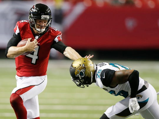 Falcons quarterback Matt Simms stiffarms Jaguars free safety Josh Evans during a preseason game Sept. 1.