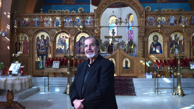 The Rev. Panagiotis Giannakopoulos, known to parishioners and friends as Father Peter, stands by the altar at St. George Greek Orthodox Church in Centerville. He will give his last liturgy before retirement Sunday.