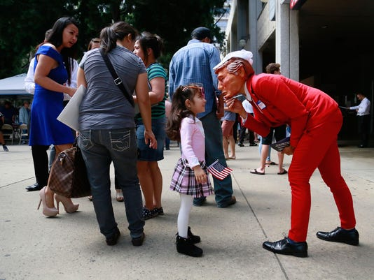 Dressed as Donald Trump, Michele Kuglitsch of the San Diego County Federation of Republican Women, right, and Ryly LeClaire, 4, of San Diego, left, meet after hundreds of new citizens were sworn in at Golden Hall.