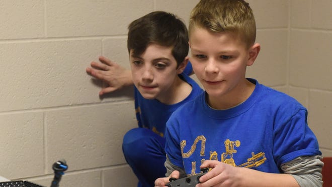 Deacon Sawyer watches as Austin Craven uses a controller to navigate a robot at Newburgh Elementary School. The school received a grant to start the VEX IQ robotics team.