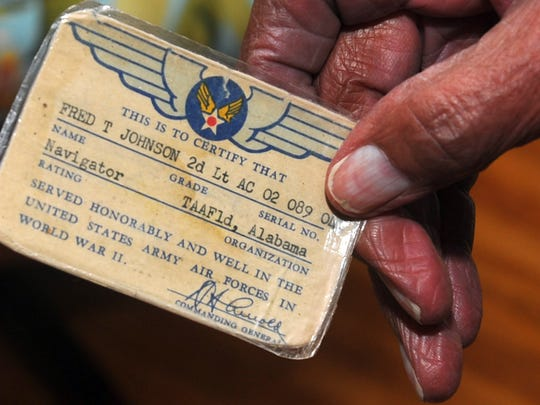 Fred Johnson holds up his discharge card as he recounts his time spent as a Tuskegee Airman in this file photo taken at his home Wednesday, December 31, 2008. Johnson joined the military in 1943 and graduated Class 42C and was commissioned as a 2nd Lt.