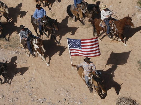 In this April 12, 2014, file photo, the Bundy family and their supporters fly the American flag as their cattle is released by the Bureau of Land Management back onto public land outside of Bunkerville, Nev.