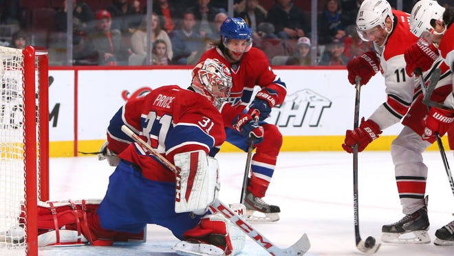 Montreal Canadiens goalie Carey Price (31) makes a save against Carolina Hurricanes center Jordan Staal (11) as defenseman Tom Gilbert (77) defends during the third period at Bell Centre.