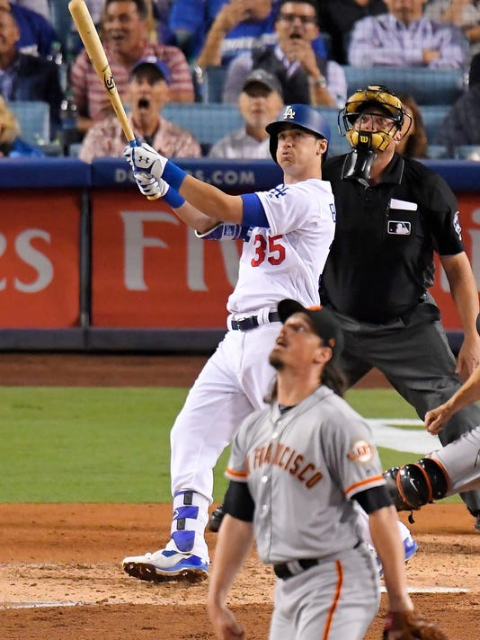 Los Angeles Dodgers' Cody Bellinger watches his three-run home run off San Francisco Giants starting pitcher Jeff Samardzija, front, during the third inning of a baseball game, Friday, Sept. 22, 2017, in Los Angeles. Nome plate umpire Bruce Dreckman is at rear. (AP Photo/Mark J. Terrill)