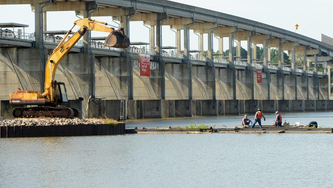 Workers reattach a barrier that broke free earlier this year on the Arkansas River near the Trimble Lock & Dam on Tuesday, Sept. 15, 2020. The barrier helps block debris from entering the Clyde T. Ellis Hydroelectric Generating Station.
