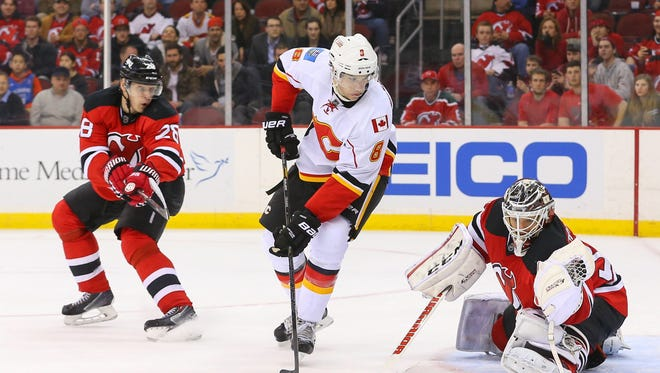 New Jersey Devils goalie Cory Schneider (35) makes a glove save through a screen by Calgary Flames center Joe Colborne (8) during the second period.