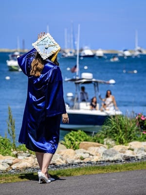 Amber Bates waves to family who boated in Plymouth Harbor to watch her graduation from Plymouth North High School.