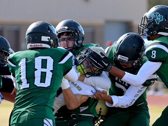 Notre Dame's Skyler Whitten (center) fights for extra yardage as five North Central Texas Academy defenders try to bring him down Friday afternoon in the TAPPS Div. III State Semifinal game at Bryson.
