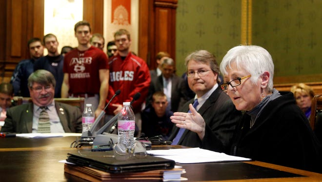 University of Iowa President Sally Mason, right, and AIB College of Business board of trustees Chairman Chris Costa speak Feb. 9 at a legislative hearing about the college's plans to close and gift its 20-acre campus to the university. Members of the AIB baseball team look on.