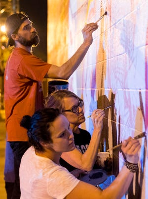 Artists Aron Conoway , Tara Remington, and Rhian Smith put paint on the wall at JBS Swift & Co as part of a mural that is two years in the making.