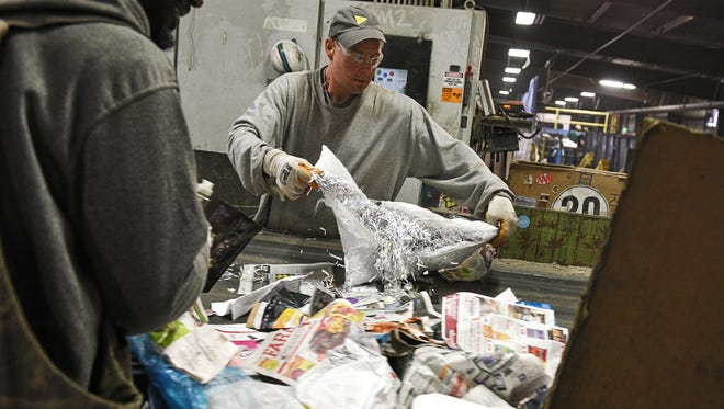 Frank Hansell, right, and Lester Simmons, left, both sorters at Millennium Recycling, sort items on a conveyor belt Tuesday, March 22, 2016, at Millennium Recycling in Sioux Falls.