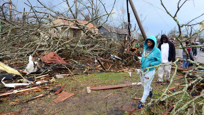 Hattiesburg residents walk past a fallen tree after the Jan. 21, 2017, tornado struck the Pine Belt.