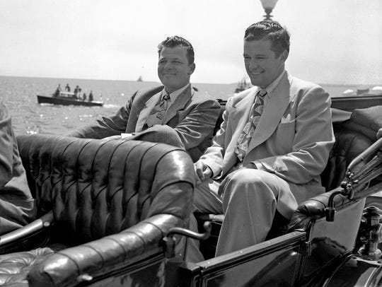 Jack Carson (left) and Dennis Morgan ride in a motorcade
