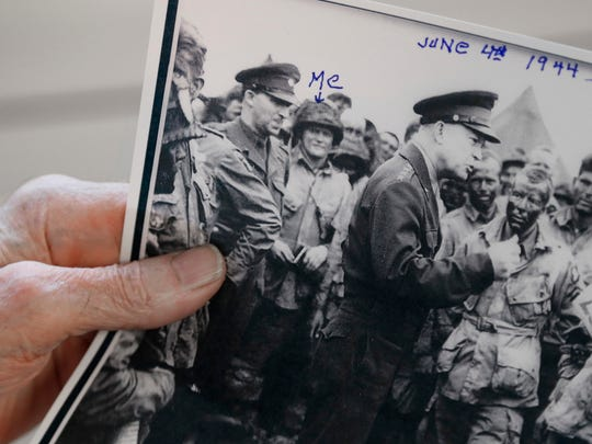 """Lindsey shows the photo of Eisenhower visiting the troops before the Normandy invasion. Just to the left of Eisenhower, holding a small sketchbook, is Lindsey. Written on the photo is the word """"Me,"""" with an arrow pointing to the 22-year-old first sergeant from Sioux City."""