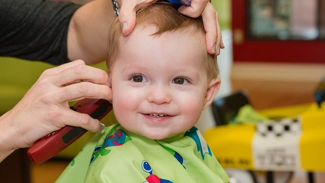 A baby gets a first haircut at Cookie Cutters Haircuts for Kids.