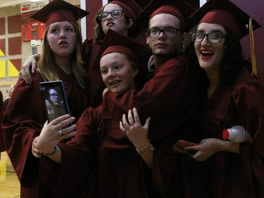 Julian Owens, 18, center, poses with her friends before the West Valley High School graduation ceremony Thursday evening.