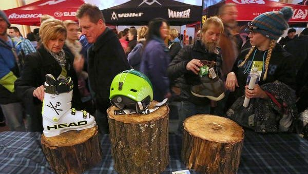 From left, Vicky Knighton and David Dumdei, both of Wausau and Brian Densow, Rhinelander, and his daughter Crystal Densow of Conover look at ski equipment at the gathering before the showing of the Warren Miller ski film at the Grand Theater in Wausau, Saturday, November 15, 2014.