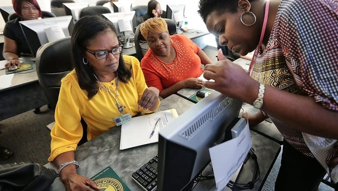 General Sessions Criminal Court Clerk Phyllis Williams, left, gets help with a new computer system called Odyssey from Laurin Osman, right, during a training class at the Vasco Smith Jr. County Administration Building.