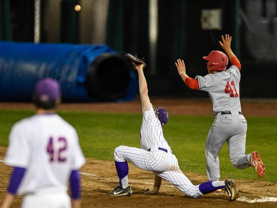 University of Southern Indiana'a Logan Brown (41) makes it to first base while a high throw goes over University of Evansville first baseman Dalton Horstmeier (14) as the University of Southern Indiana Screaming Eagles play the University of Evansville Aces at Evansville's Braun Stadium on April 25, 2018.
