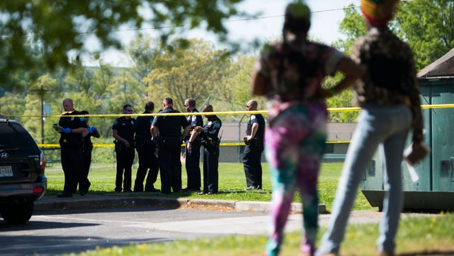 Bystanders watch as officers communicate at the scene of a shooting at Montgomery Village on Tuesday, May 1, 2018.