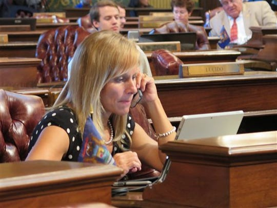 Michigan Rep. Cindy Gamrat, R-Plainwell, sits at her desk on the House floor while Republicans head into a closed-door meeting on road funding on Tuesday, Aug. 18, 2015, in Lansing, Mich.