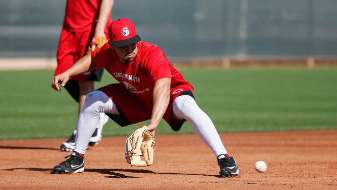 Cincinnati Reds third baseman Eugenio Suarez (7) fields a ground ball during drills at Cincinnati Reds spring training, Saturday, Feb. 20, 2016, in Goodyear, Arizona.