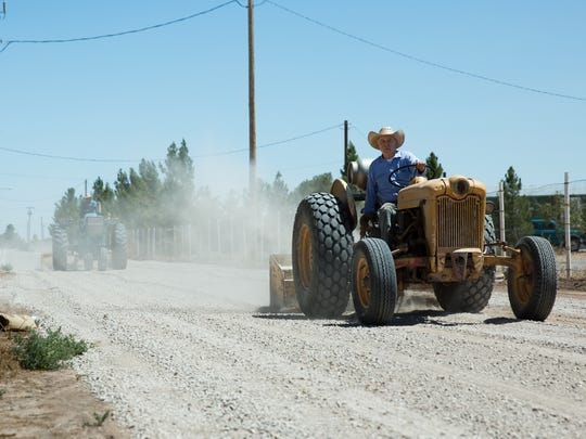Mesquite residents Hilario Gomez, right, and Esequiel Chavez smooth a newly graveled Tres Caballos road on Tuesday July 12, 2016. Resident who live in homes on the road pitched in hundreds of dollars each to fix the privately owned road themselves.