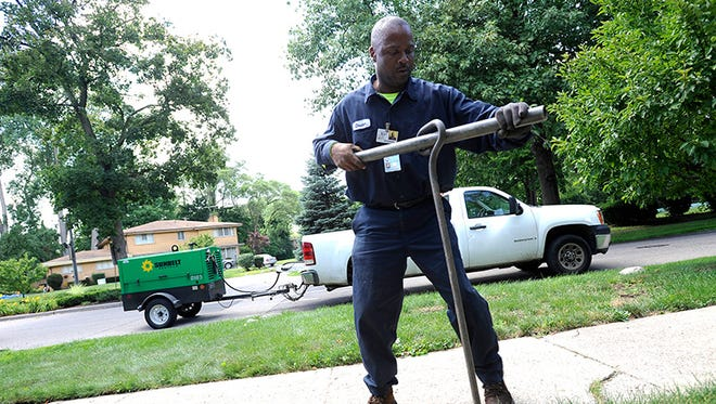 Chester Clemons, a water shut-off technician for the city of Detroit, shuts off water at a home in Palmer Woods neighborhood in Detroit on July 8, 2014.