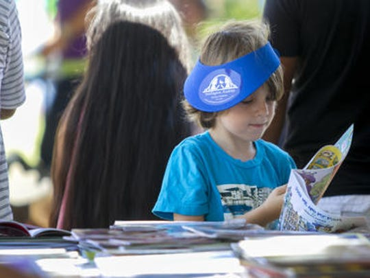 Riley Williams, 5, picks out a free book at the Southwest Florida Reading Festival. The  festival returns  Saturday to downtown Fort Myers.