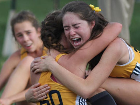The St. Ursula cross country team celebrates after itsfinish at the District A meet at VOA Park, Saturday.