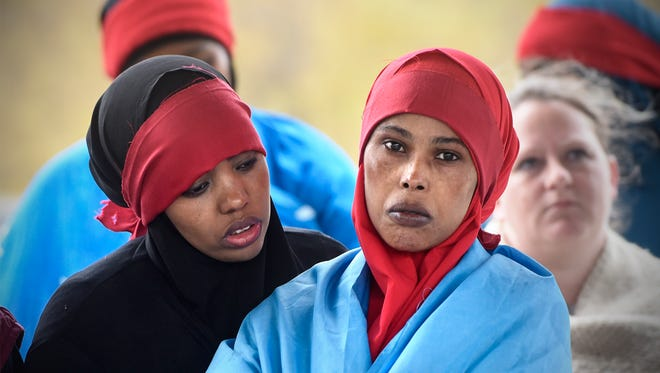 Community members listen as several speakers share their thoughts during a vigil mourning the victims of the recent bombing in Mogadishu Saturday, Oct. 21, at Lake George in St. Cloud.