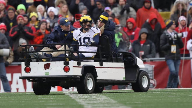 Michigan's  Brandon Peters being taken to the locker room after a hit during the third quarter Saturday, Nov. 18, 2017, at Camp Randall Stadium in Madison, Wis.