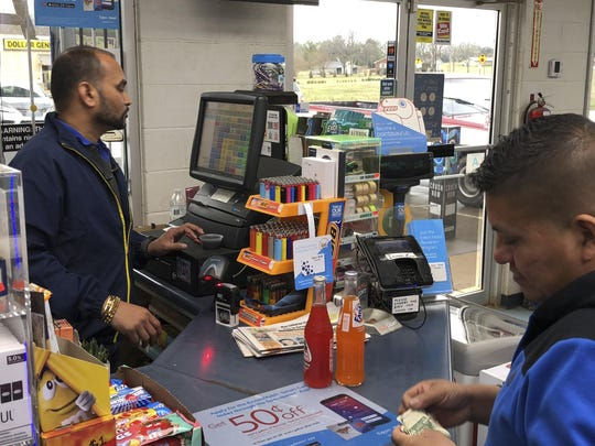 Jee Patel checks out a customer at the KC Mart on Tuesday, Feb. 19, in Simpsonville, South Carolina. The store sold the only Mega Millions ticket to win the $1.5 billion jackpot in October 2018. The ticket has not been claimed.