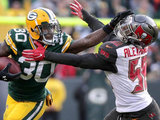 Green Bay Packers running back Jamaal Williams stiff-arms Tampa Bay Buccaneers middle linebacker Kwon Alexander in overtime at Lambeau Field.