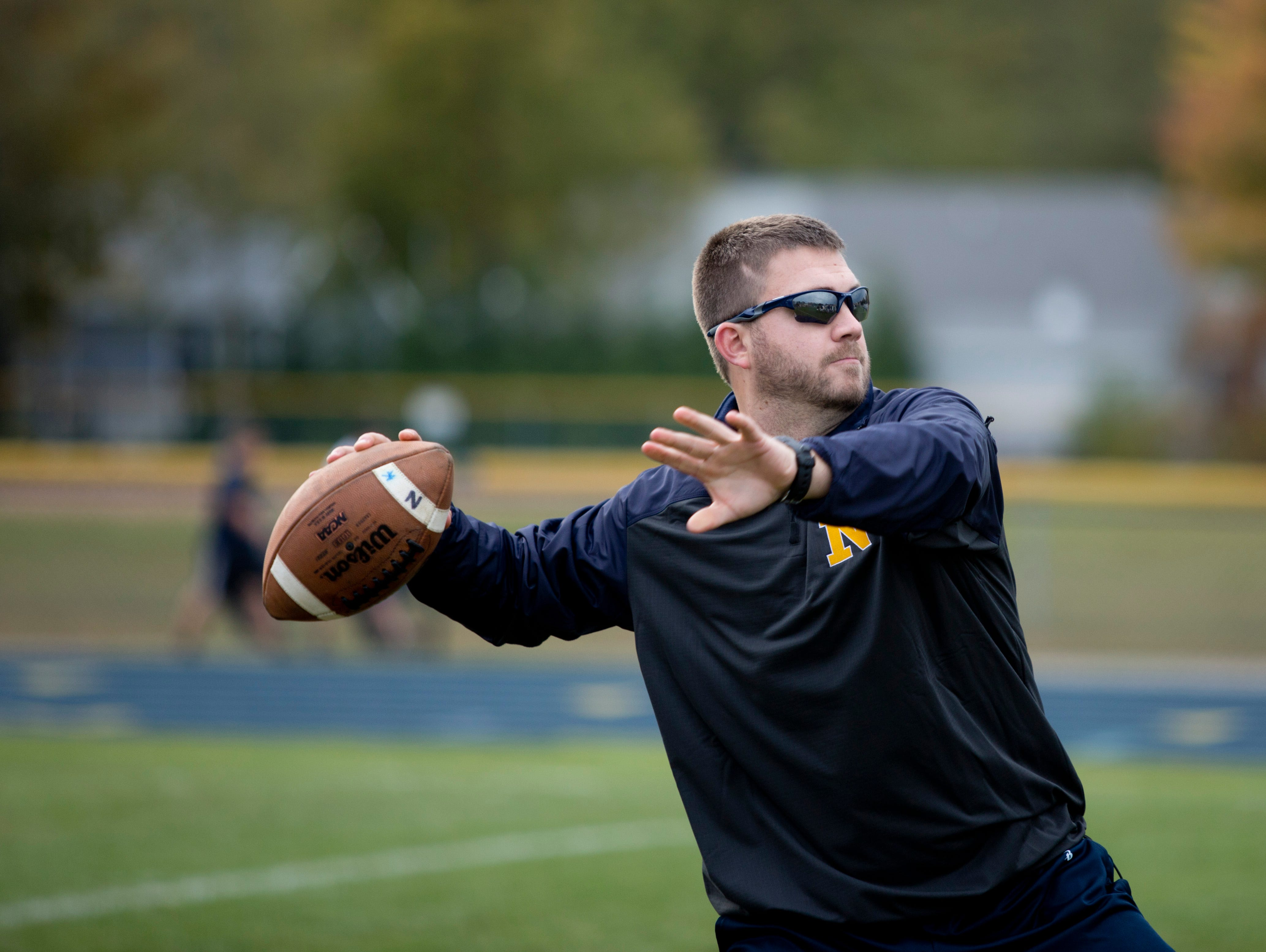 Coach Larry Roelens throws a pass to players during practice Wednesday, October 21, 2015 at Port Huron Northern High School.