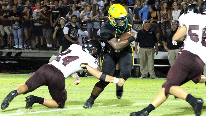 Catholic's Abram Smiley breaks a tackle attempt by Navarre's Reese Parker (24).